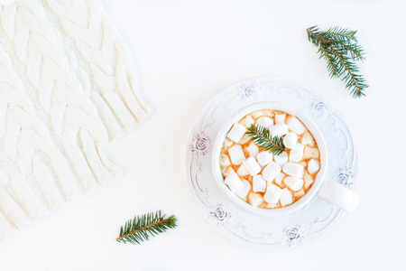 Christmas hot drink, coffee with small marshmallows, fir cones and branches.  White table, top view, flat lay.