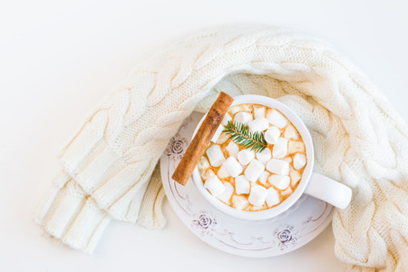 Cozy warm knitted scarf and cacao with marshmallows and cinnamon in vintage cup.  White table, top view, flat lay.