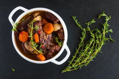 Beef Bourguignon in a white soup bowl on black stone background, top view. Stew with carrots, onions, mushrooms, bacon, garlic and bouquet garni. The dish is served with fresh thyme. Zdjęcie Seryjne - 68287505