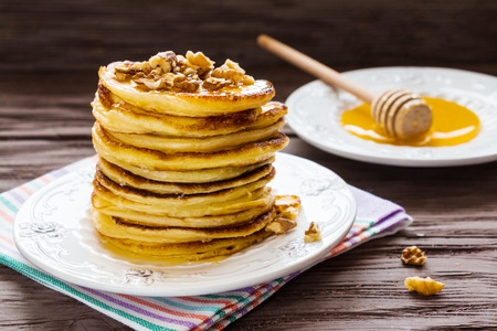 Homemade pancakes with honey and walnuts, vintage white plate, dipper, dark wooden table. Zdjęcie Seryjne