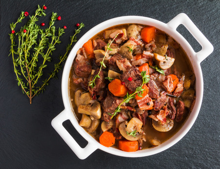 Beef Bourguignon in a casserole on black stone. Stewed with bacon, garlic, carrots, onions, mushrooms,  red wine, fresh thyme and spices. Top view. Zdjęcie Seryjne