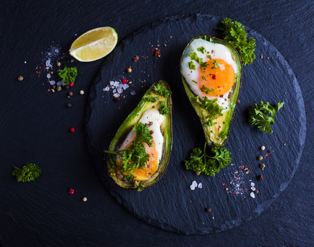 Avocado baked with eggs, fresh parsley, ground pepper. Black stone background, top view.