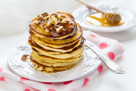 Stack of homemade pancakes with honey and walnuts, vintage plate and fork, dipper, white background. 版權商用圖片