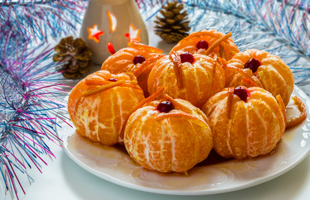 Christmas decoration, peeled whole tangerine in caramel with citron, burning candle, white table, bright garland. Zdjęcie Seryjne