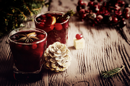 Christmas decoration and mulled wine with cranberries, anise and oranges. Dark wooden background, vintage effect, toned image. Zdjęcie Seryjne