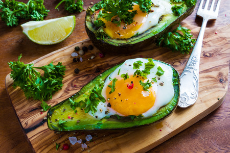 Avocado baked with eggs. Wooden background, fresh parsley, ground pepper.