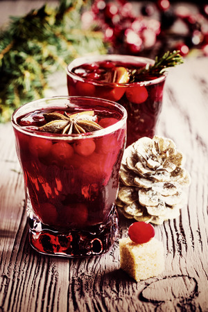Christmas decoration and mulled wine with cranberries, anise and oranges. Dark wooden background, vintage effect, toned image. 版權商用圖片