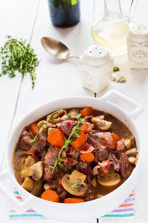 白いテーブルに鍋で牛肉の煮込み。ベーコン、ニンニク、ニンジン、玉ねぎ、マッシュルーム、スパイス煮込み。新鮮なタイム、ビンテージ スプー 写真素材