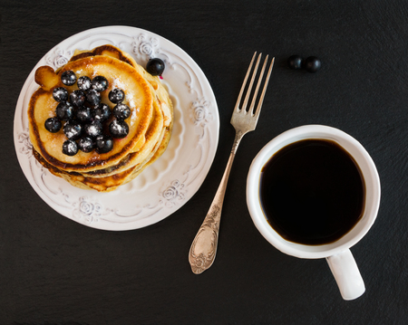 Homemade pancakes and black currant, vintage white crockery, cup of coffee, black stone background, top view.