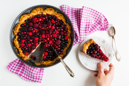 Open round cake with berries, raspberries, blackberries, red and black currant jelly. Shortbread dough, a layer of cheese. White  table, top view. Zdjęcie Seryjne