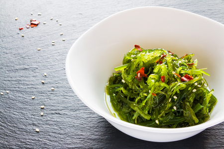 Traditional japanese chuka wakame salad with sesame seeds in white bowl on black stone.