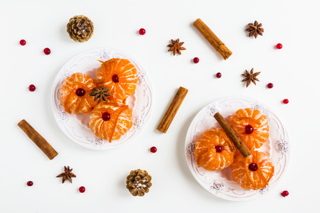Christmas background, peeled whole tangerine in caramel, citron, cinnamon sticks, anise stars on white, top view, flat lay.