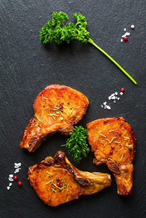 Roasted pork steaks, cutlets with bones  and fresh parsley on black stone background, top view.