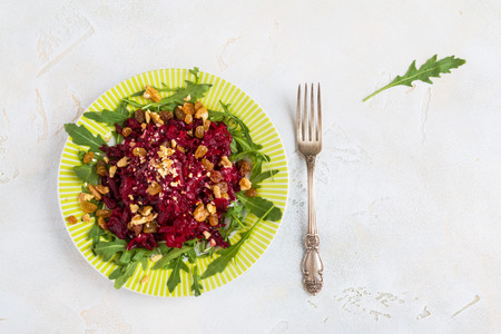 Salad with baked beets, arugula, raisins and walnuts on a green plate with vintage fork on the table in kitchen. Food background with copy space, top view, flat lay. 版權商用圖片