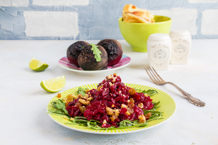 Salad with baked beets, arugula, raisins and walnuts on a green plate on the table in kitchen. Whole beetroots, lime, fresh bread, vintage fork.