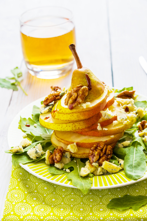 Fruit salad, whole pear sliced,  walnuts caramelized in honey, blue cheese and arugula. Green plate on wooden table, vintage knife and fork, vertical photo.