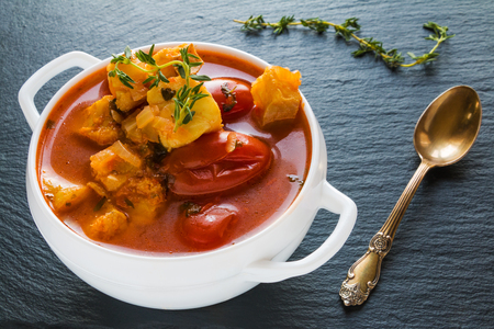 Fish soup with cod, tomato, onion, garlic and thyme in white bowl on black stone background.