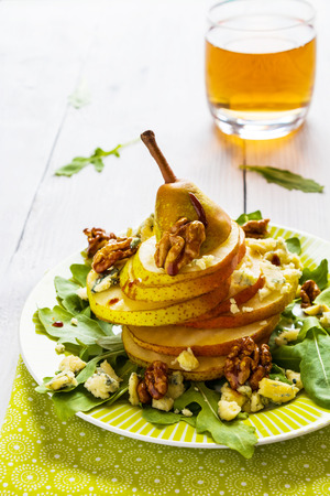 Fruit salad, whole pear sliced,  walnuts caramelized in honey, blue cheese and arugula. Green plate on white wooden table. Stock Photo