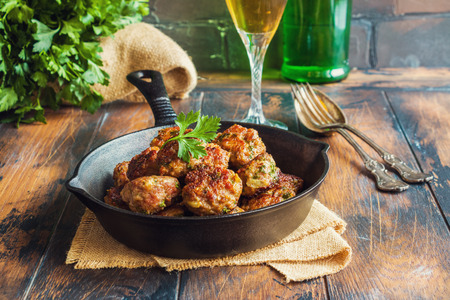 Homemade roasted beef meatballs in cast-iron pan on wooden table in kitchen. Stock Photo
