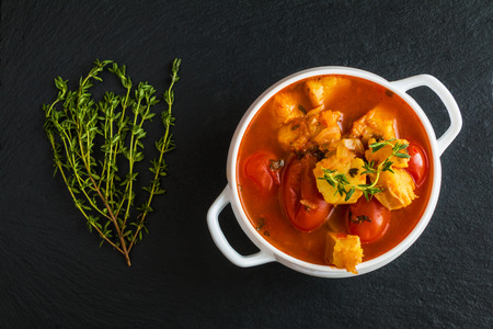 Fish soup with cod, tomato, onion, garlic and thyme in white bowl on black stone background, top view. Zdjęcie Seryjne - 68379389