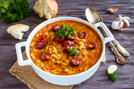 Tomato soup with orzo and smoked sausages in white casserole on wooden rustic table. Fresh bread and parsley, vintage spoon.