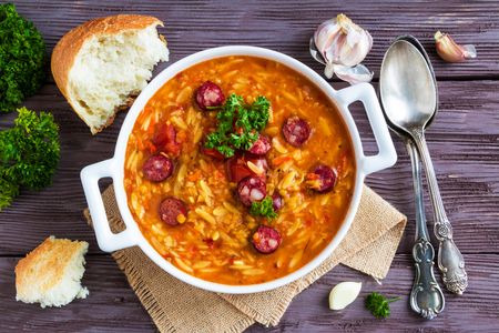 Tomato soup with orzo and smoked sausages in white casserole on wooden rustic table. Fresh bread and parsley, vintage spoon, top view. Stock Photo