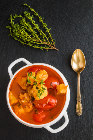 Fish soup with cod, tomato, onion, garlic and thyme in white bowl on black stone background, top view.