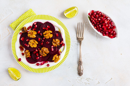 Dietary vegetarian salad of roasted beets with pomegranate seeds, walnuts caramelized in honey and natural yoghurt. Slices of lime, vintage fork, white and gray table, top view. Stock Photo