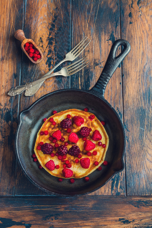 Homemade fried pancakes on a black cast iron skillet. Above are berries, raspberries, cranberries and blackberries. Wooden rustic brown background, vintage forks, top view.