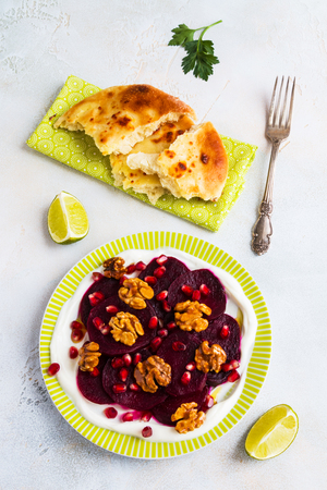 Dietary vegetarian salad of roasted beets with pomegranate seeds, walnuts caramelized in honey and natural yoghurt. Slices of lime, freshly baked bread, vintage fork, white and gray table, top view.