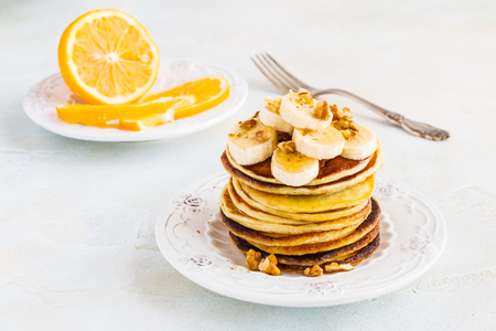 Stack of homemade pancakes with banana, maple syrup and walnuts on vintage plate. Fork, fresh sliced lemon, white and gray concrete background. Zdjęcie Seryjne - 69901824