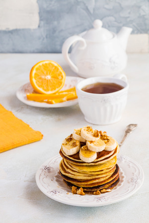 Stack of homemade pancakes with banana, maple syrup and walnuts on vintage plate. Fork, fresh sliced lemon, cup of tea and teapot, white and gray concrete background.
