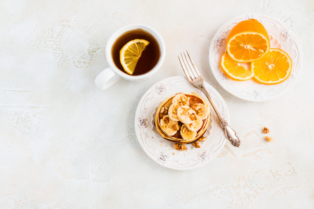 Stack of homemade pancakes with banana, maple syrup and walnuts on vintage plate. Fork, fresh sliced fresh lemon, cup of tea, white and gray concrete background, top view. Stok Fotoğraf - 69913528