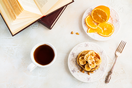 Stack of homemade pancakes with banana, maple syrup and walnuts on vintage plate. Fork, fresh sliced fresh lemon, cup of tea, white and gray concrete background, top view.