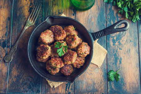 Homemade roasted beef meatballs in cast-iron skillet on wooden table in kitchen, fresh parsley, vintage fork, top view. Stock Photo