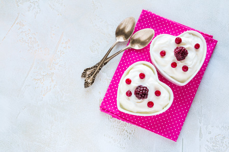 Valentine day decoration, breakfast, yogurt with berries for two in white heart-shaped bowls on the table. Top view, flat lay. Stock Photo
