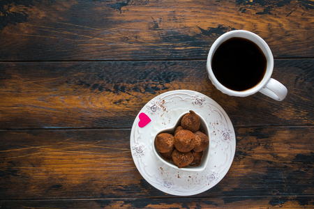 Valentine day, white vintage plate, sweets and heart made from red paper, cup of black coffee. Top view, flat lay, wooden rustic table.