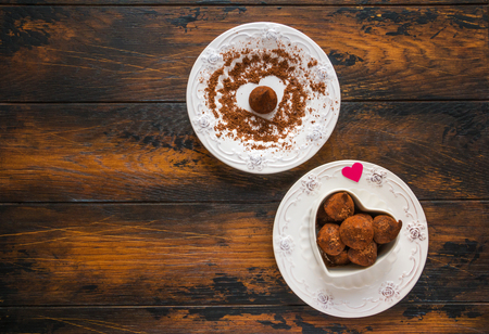 Valentine day, white vintage plates, sweets and hearts made from red paper and grated chocolate. Top view, flat lay, wooden rustic table. Stock Photo