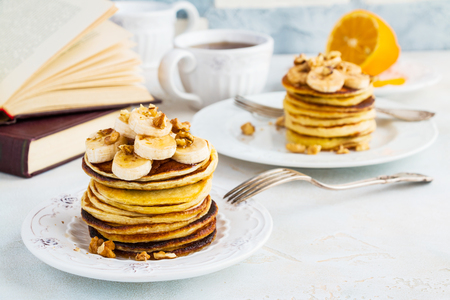 Stack of homemade pancakes with banana, maple syrup and walnuts on vintage plate. Fork, fresh sliced fresh lemon, cup of tea, open book, white and gray concrete background. 版權商用圖片 - 69984704