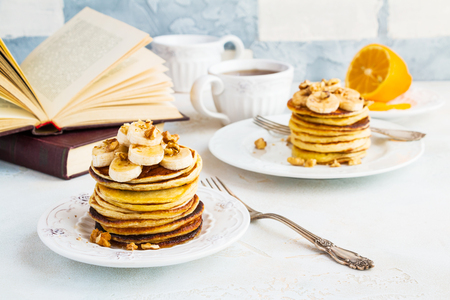 Stack of homemade pancakes with banana, maple syrup and walnuts on vintage plate. Fork, fresh sliced fresh lemon, cup of tea, open book, white and gray concrete background.