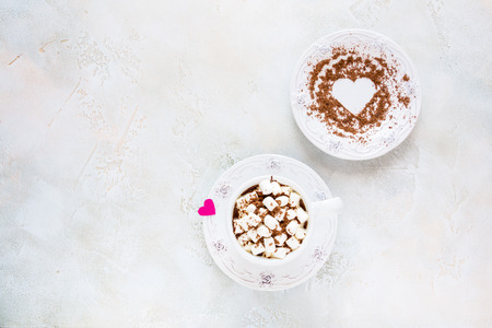 Valentine day decoration, breakfast, white vintage cup and plate, coffee with small marshmallows and hearts made from red paper and grated chocolate. Top view, flat lay.