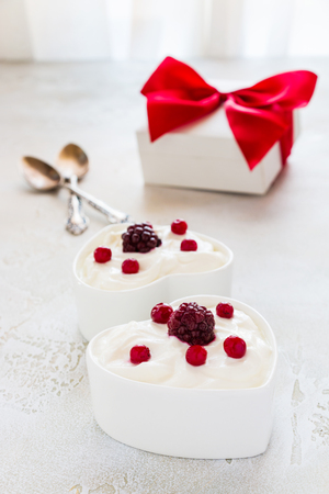 Valentine day decoration, breakfast, yogurt with berries for two in white heart-shaped bowls on the table.