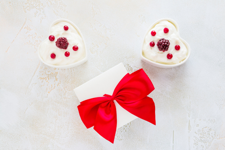 Valentine day decoration, breakfast, yogurt with berries for two in white heart-shaped bowls and gift box on the table. Top view, flat lay. Stock Photo