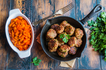 Homemade roasted beef meatballs in cast-iron skillet and beans baked in tomato sauce in baking dish on wooden table in kitchen, fresh parsley, vintage fork, top view. Stock Photo