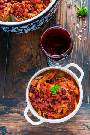 Beans with pork stewed in spicy tomato sauce with onion, paprika, beer, bell and pink pepper. White soup bowl, casserole, glass of red wine and fresh parsley on wooden rustic table, top view.