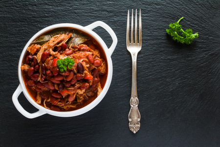 Beans with pork stewed in spicy tomato sauce with onion, paprika, beer, bell and pink pepper. White soup bowl, vintage fork and fresh parsley on black stone, top view. Zdjęcie Seryjne