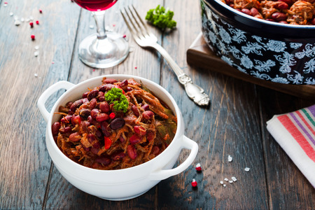 Beans with pork stewed in spicy tomato sauce with onion, paprika, beer, bell and pink pepper. White soup bowl, casserole, glass of red wine and vintage fork on wooden rustic table.