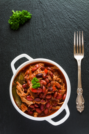 Beans with pork stewed in spicy tomato sauce with onion, paprika, beer, bell and pink pepper. White soup bowl, vintage fork and fresh parsley on black stone, top view. Stock Photo