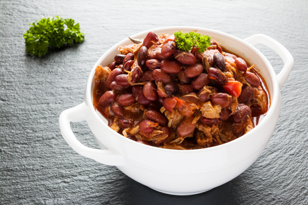 Beans with pork stewed in spicy tomato sauce with onion, paprika, beer, bell and pink pepper. White soup bowl and fresh parsley on black stone. Stock Photo