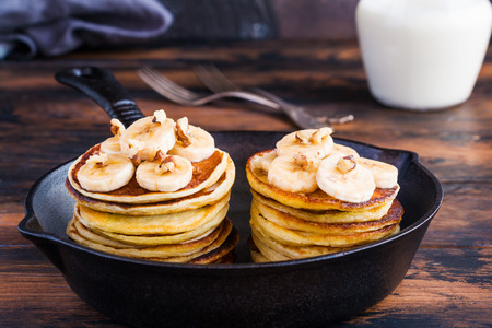 Stack of homemade pancakes with banana, maple syrup and walnuts in black cast iron skillet. Vintage forks, glass jar with milk, wooden rustic table.